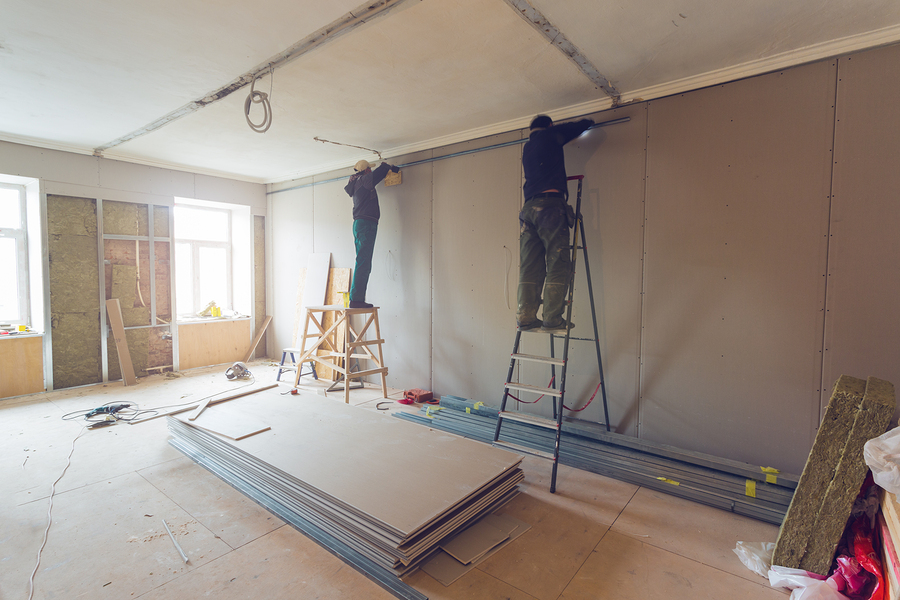 workers are installing plasterboard