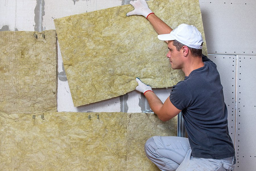 worker insulating a room wall with mineral rock wool thermal insulation.